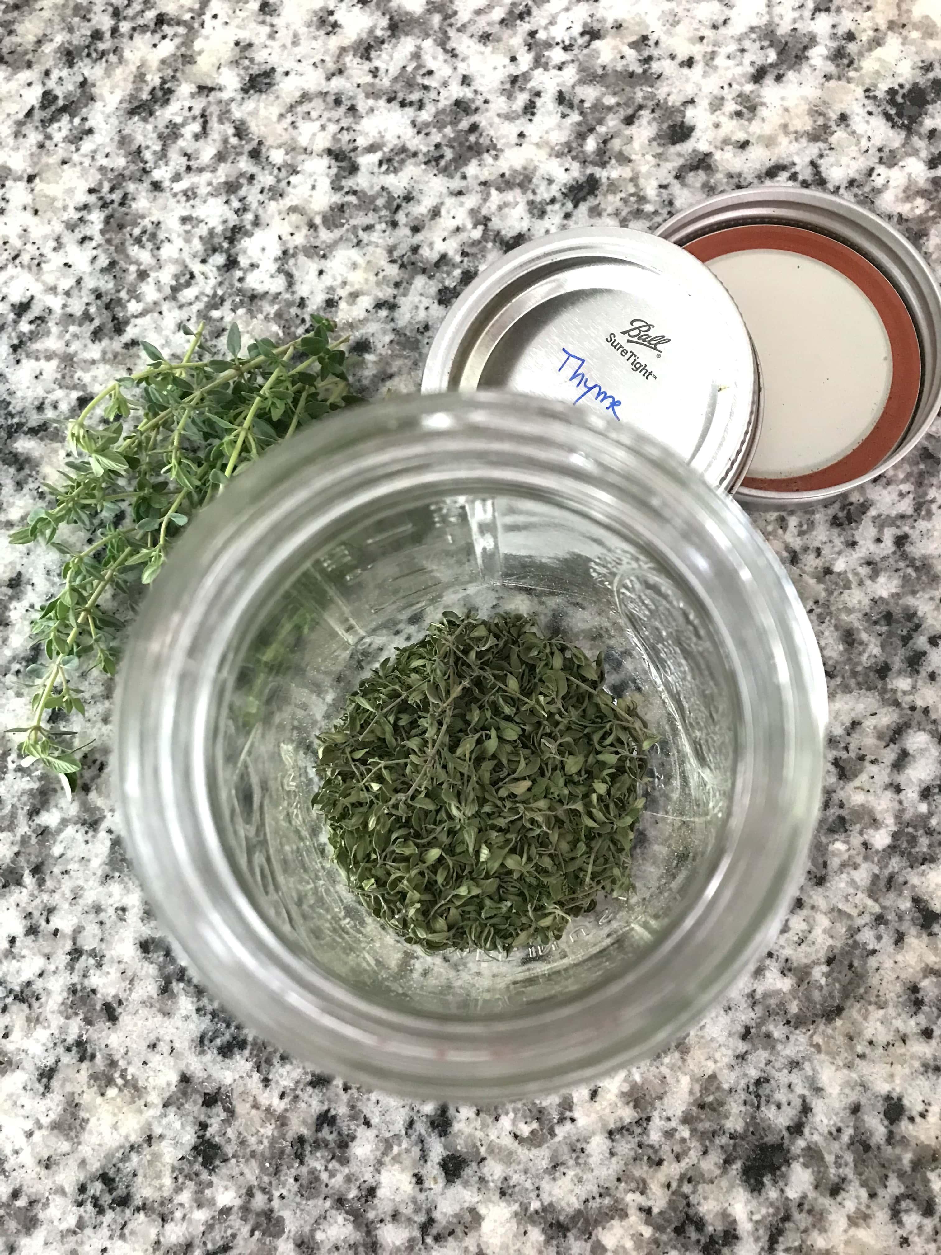 Overhead shot of a mason jar full of dried thyme; how to preserve fresh herbs