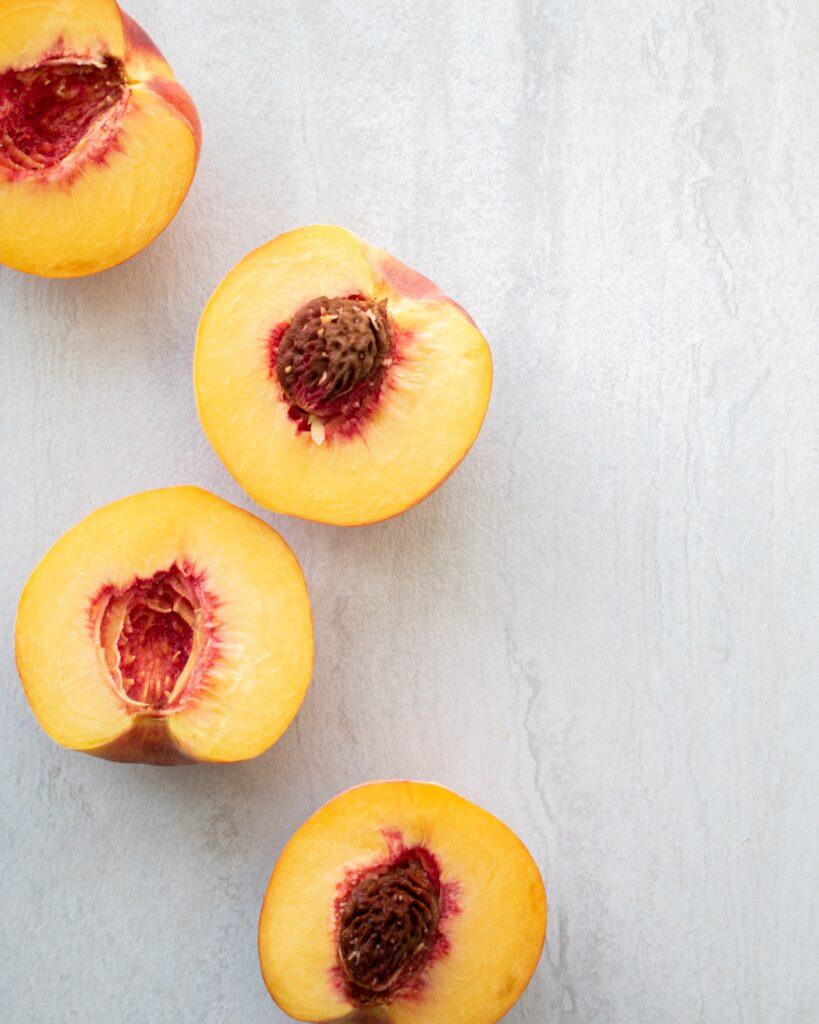 Overhead shot of four peach halves on a white countertop – peach pepper jam